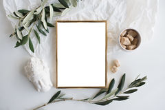Golden frame mock-up on white tabletop. Background, home decor flatlay with plants and objects Stock Image