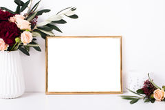 Golden frame mock-up on white wall. Background, home decor with flowers and objects Stock Photos