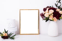 Golden frame mock-up on white wall. Background, home decor with flowers and objects royalty free stock photo