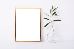 Golden frame mock-up on white wall. Background, home decor with flowers and objects Stock Images