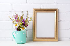 Golden frame mockup with chamomile and purple flowers in mint g royalty free stock photo