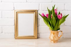 Golden frame mockup with magenta pink tulips in golden vase. Golden frame mockup with bright magenta pink tulip bouquet in the golden vase. Empty frame mock up stock photo