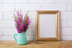 Golden frame mockup with maroon purple flowers in mint pitcher royalty free stock photography