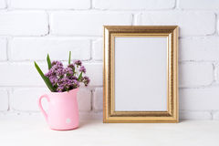Golden  frame mockup with purple flowers in pink rustic pitcher. Golden frame mockup with purple field flowers in polka dot pink rustic pitcher vase. Empty frame Royalty Free Stock Photography