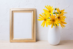 Golden frame mockup with yellow rosinweed flowers in vase royalty free stock image
