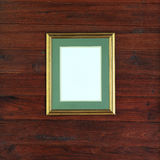 Golden frame photo on wood wall Stock Images