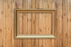 Golden frame picture on wood. Royalty Free Stock Image