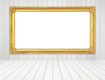 Golden frame in room with white wood wall and wood floor backgro Royalty Free Stock Photo