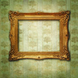 Golden frame on vintage green wallpaper. Empty baroque golden frame on an aged wallpaper with floral decorations and grunge effects vector illustration