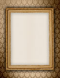Golden frame on wallpaper background. Old golden frame on floral background Stock Image