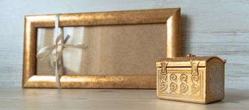 Golden frame with a white bow and golden chest on the grey wooden background royalty free stock images
