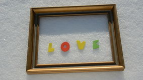 Golden frame on winter snow and word love Stock Images