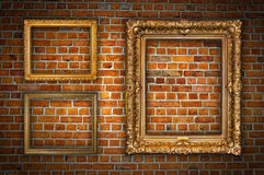 Golden frames on brick wall. Old ornate golden frames hanging on a brick wall Stock Images