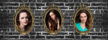 Golden frames with woman portraits on brick wall Stock Photography