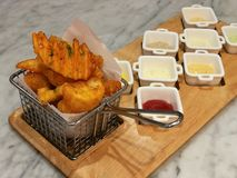Golden French fries serving in the basket with 8 dipping sauces, ketchup and mayo, stylist food, fusion food. Background Stock Photo