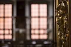 Golden fresco ornamental head on a door in a noble room stock image