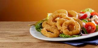 Golden fried calamari rings with fresh salad. Golden fried calamari rings with fresh Greek salad served on a platter on a wooden counter with copy space in Royalty Free Stock Photography