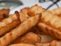 French Fries in Macro. Golden fried crinkle cut french fries in macro. On a plate waiting for lunchtime consumption royalty free stock photo