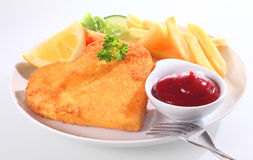 Golden fried escalope or schnitzel. In breadcrumbs with a side dish of ketchup or tomato sauce served with a slice of lemon and French fries royalty free stock images