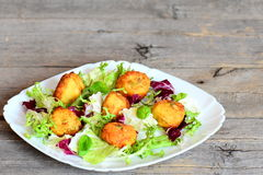 Golden fried mashed potato cutlets with pumpkin seeds served with fresh lettuce mix and basil on a plate Stock Image