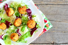 Golden fried potato balls with pumpkin seeds served with lettuce mix and basil on a plate Royalty Free Stock Photo