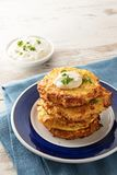 Golden fried rosti pile from cauliflower and parmesan cheese wit. H a creamy dip and parsley garnish, blue napkin, bright wooden table with copy space, vertical Stock Images