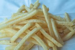 Golden fries on white background. Yellow french fries with wooden sauce cup on plain floor. Copy space. Calories chip chips closeup crispy crunchy delicious royalty free stock images