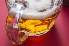 Golden frothy beer on a glass jar Royalty Free Stock Image