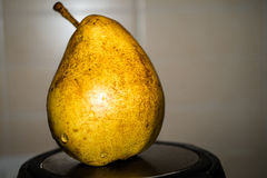 Golden fruit. Pear on the stand Stock Photo