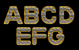 Golden A-G letters incrusted with diamonds Stock Images