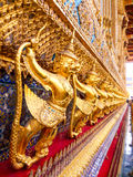 Golden Garuda catching Naga sculpture at Wat Phra Kraw, Bangkok. Golden Garuda catching Naga sculpture at Wat Phra Kraw in the Grand Palace, Bangkok Royalty Free Stock Image