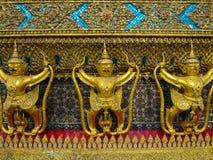 Golden garuda holding naga statue fully front view with ornament. Golden garuda holding naga statue fully front view with glass mosaic and other ornamental Stock Photo