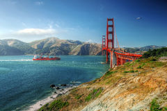 Golden Gate Bridge. Unique perspective of Golden Gate Bridge with a cargo ship and seagull, framed by beautiful mountains, pacific ocean and land in the evening stock photography