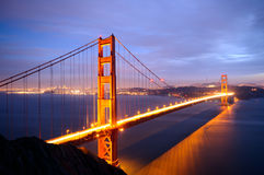 Golden Gate Bridge from Battery Spencer viewpoint. Glows in the dusk after a spring storm with San Francisco skyline in the background Royalty Free Stock Photo