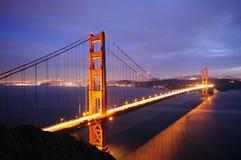 Golden Gate Bridge and Bay Bridge glow in the dusk. Golden Gate Bridge glows against backdrop of illuminated Bay Bridge and San Francisco skyline Stock Images