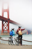 Golden gate bridge - biking couple sightseeing. In San Francisco, USA. Young couple tourists on bike tour enjoying the view at the famous travel landmark in Royalty Free Stock Photo