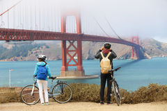 Golden gate bridge - biking couple sightseeing. In San Francisco, USA. Young couple tourists on bike tour enjoying the view at the famous travel landmark in Stock Photos