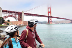 Golden gate Bridge biking tourists on guided tour. Golden gate bridge - biking couple sightseeing in San Francisco, USA. Young couple tourists on bike guided Stock Photo
