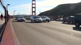 Golden Gate bridge with cars coming right past the camera. Shot from the pedestrian walkway stock video footage