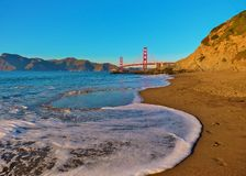 Golden Gate Bridge close up from Baker Beach before sunset. Waves rolling in a the Golden Gate Bridge on Baker Beach just before sunset royalty free stock photo