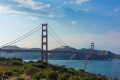 Golden Gate Bridge with Commercial Ship. A container ship passes under the Golden Gate Bridge on a cloudy day. A bank of fog is starting to creep over the hills Stock Photo