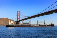 Golden gate bridge en vrachtschip op zonnige dag Royalty-vrije Stock Foto's