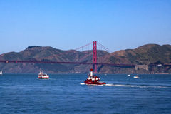 Golden Gate Bridge - Ferry - Fireboat. Fire Boat Guardian and a Red and White Ferry sail toward the Golden Gate Bridge in this photo, taken during Opening Day on Royalty Free Stock Image