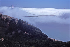 Golden Gate Bridge in the Fog. Dense fog bank envelopes the Golden Gate Bridge with rocky hills in the foreground Stock Photography