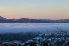 Golden Gate Bridge in fog. At sunset, with fog rolling over the San Francisco Bay and the University of California Saint Ignatius Church in the foreground Stock Photos