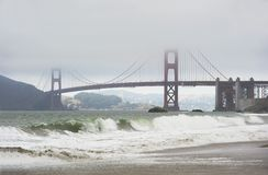 Golden gate bridge in fog and waves Royalty Free Stock Photos
