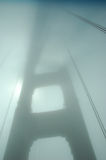 Golden Gate Bridge foggy silhouette. A tower of the Golden Gate Bridge is shrouded in fog and silhouetted by the sun Royalty Free Stock Image