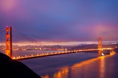 The Golden Gate Bridge glows just before sunrise. The iconic Golden Gate Bridge in San Francisco on a cloudy pre-dawn morning Stock Photography