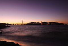 Golden gate bridge i magiskt ögonblick på skymningtid, med det silkeslena havet Arkivbild