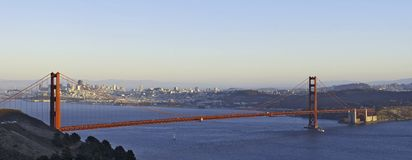 Golden Gate Bridge lit by the. A panoramic image of Golden Gate Bridge lit by the setting sun with the San Francisco skyline in the background Stock Photos